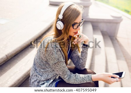 Summer lifestyle sunny image of pretty young blonde woman listening to music by earphones , holding mobile phone, sitting on the street,  dreaming. Wearing stylish spring outfit.  - stock photo
