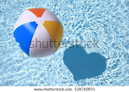 Summer love, Beach Ball on the swimming Pool with heart shaped shadow - stock photo