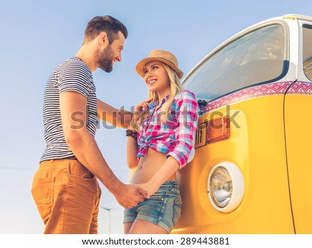 Summer love. Low angle view of happy young couple holding hands and looking at each other while standing near their retro minivan - stock photo
