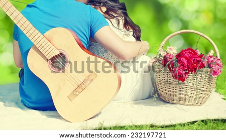 Summer, love, vacation and people concept - lovely young couple in love resting together on the grass near basket with bouquet flowers, man with acoustic guitar hugs his beloved woman outdoors - stock photo