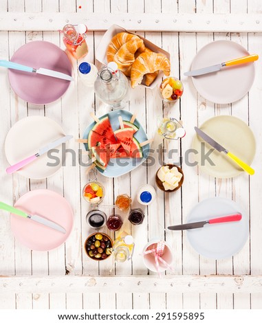 Summer lunch served on a wooden picnic table outdoors with croissants, olives, preserves, butter, watermelon and fruit juice between two rows of empty plates with knives, overhead view - stock photo