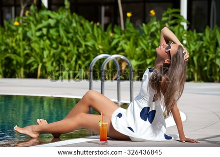 Summer luxury vacation. Sexy cheerful woman in summer dress relaxing at the luxury poolside. Girl at travel spa resort pool.  - stock photo