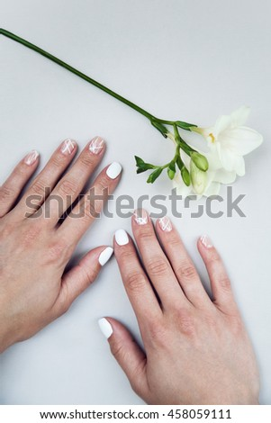 Summer manicure for the bride in gentle tones with bright pink flowers. Nail Design. Close-up.