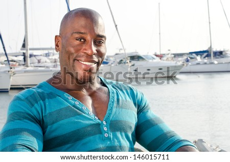 Summer marine scene with a handsome black man. Attractive man wearing a blouse with stripes at the sea side. Yachts in the background. - stock photo