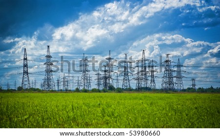 summer meadow with high-voltage towers row - stock photo