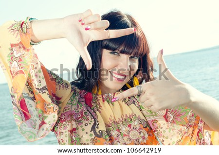 Summer memories: smiling young woman on the shore making a frame with her fingers - stock photo