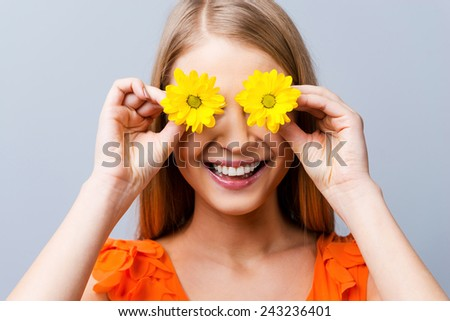 Summer mood. Beautiful young woman in pretty dress holding flowers in front of her eyes while standing against grey background   - stock photo