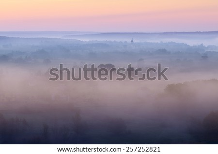Summer morning. Fog in the valley above the river. Dome of the Church in the mist - stock photo