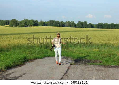 Summer morning in wheat field. Woman walks on a footpath. - stock photo