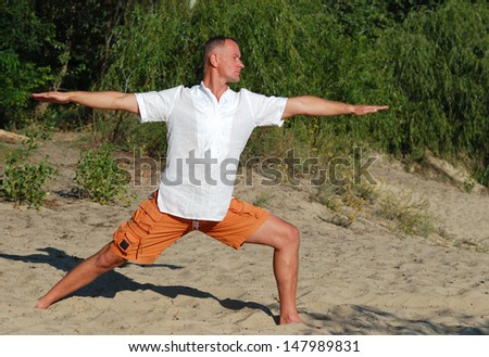 Summer morning on the beach. A man practices yoga in nature - stock photo