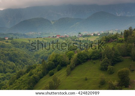 Summer mountain landscape above the hills. Villlage view at Moeciu - Bran, Romania - stock photo