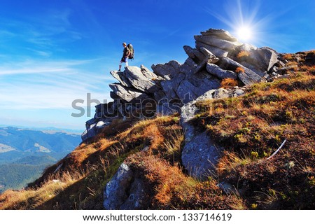 Summer mountain landscape with tourist on cliff - stock photo