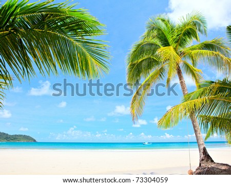 Summer nature view - palm trees on white sand and blue sea - stock photo