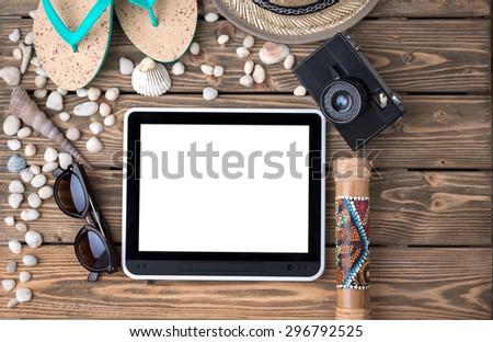 Summer objects for vacation organized around tablet PC. Flip-flops, straw hat, sunglasses and photocamera among sea shells and stones on wooden.  - stock photo