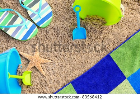 Summer on the Sand: Beach towel surrounded by color coordinated beach accessories and starfish suggest a summer beach vacation. Great background, stock, concept, vacation/recreation, and travel image. - stock photo