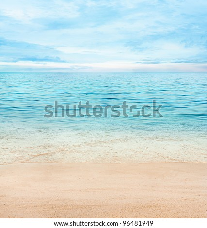Summer or spring abstract background. Golden sand with blue ocean and cloudscape and sunset in the back. - stock photo