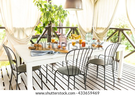 Summer outdoor continental breakfast on the garden terrace. Countryside weekend or rural holiday scenery. - stock photo