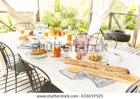 Summer outdoor continental breakfast on the garden terrace. Countryside weekend or rural holiday scenery.