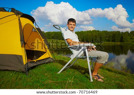 summer outdoor portrait of handsome man sitting in folding chair near camp tent