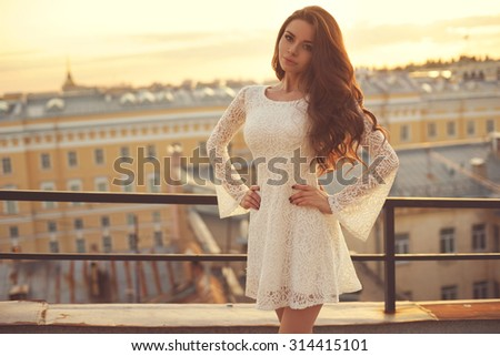 Summer outdoor portrait of young pretty elegant girl posing at roof at sunset. Lovely soft back light. View on city buildings and roofs. - stock photo