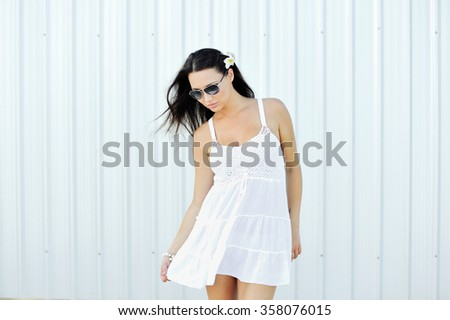 Summer outdoor portrait of young pretty elegant girl posing on white wall - stock photo