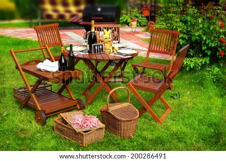Summer Party or Picnic Scene. Outdoor furniture on the lawn. BBQ Grill in blurred background. - stock photo