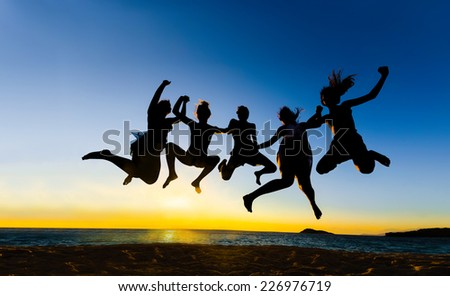 Summer party people jumping for joy, fun at vibrant sunset sky