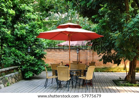 Summer Patio with tables and wooden chairs under umbrella in garden - stock photo