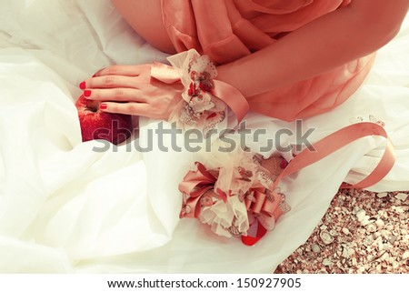 Summer picnic concept. Hand of sitting woman in trendy dress holding red apple (love symbol). Wedding accessories on white vapory cloth. Sunny weather. Outdoor shot