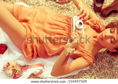 Summer picnic concept. Portrait of a happy young woman lying at the seaside in trendy dress, holding vintage photo-camera and shooting something. Sunny weather. Outdoor shot - stock photo