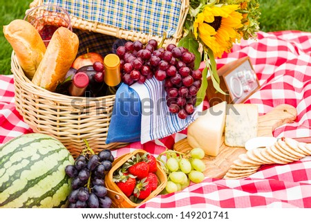 Summer picnic with a basket of food in the park. - stock photo