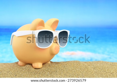Summer piggy bank with sunglasses on beach - stock photo
