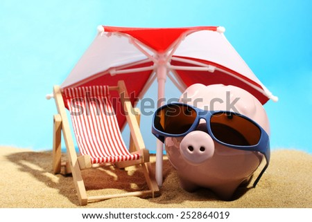Summer piggy bank with sunglasses standing on sand under red and white sunshade next to beach chair  - stock photo