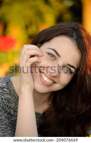 Summer portrait of a beautiful freckled young woman smiling with colorful background - stock photo