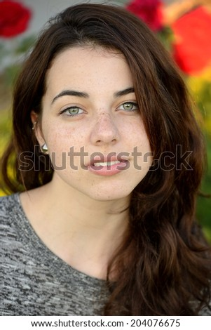 Summer portrait of a beautiful freckled young woman with colorful background - stock photo