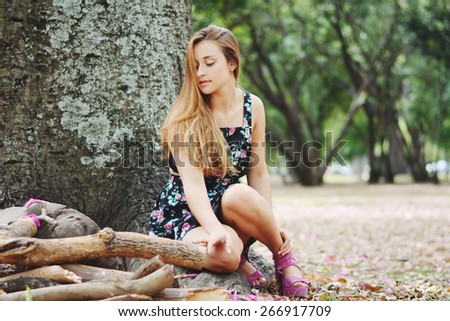 Summer portrait of a beautiful young girl in park. - stock photo