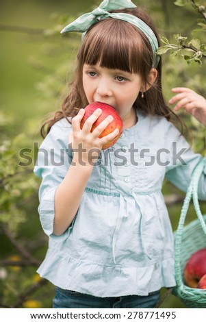 Summer portrait of a cute girl with apples