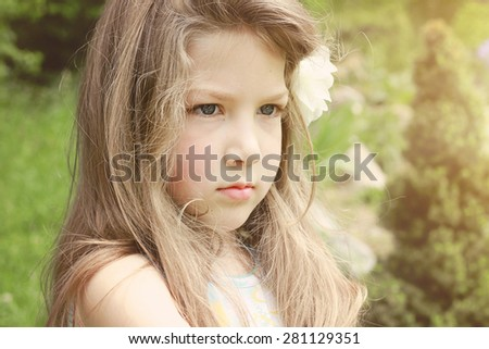 Summer portrait of a cute little girl with flower in her hair