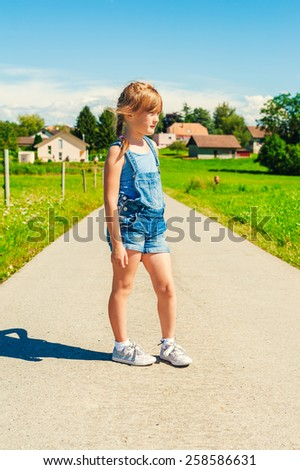Summer portrait of a little girl of 6 years old, wearing denim overalls and grey shoes,  - stock photo