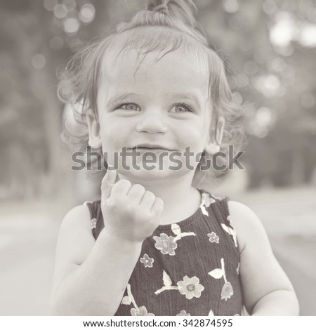 Summer portrait of beautiful baby girl. Black and white image. Kid smiling and looking at camera. - stock photo
