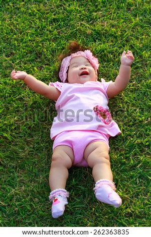 Summer portrait of beautiful baby girl happy on the lawn - stock photo