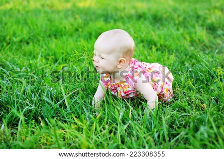 Summer portrait of beautiful baby girl  in colorful dress on the lawn