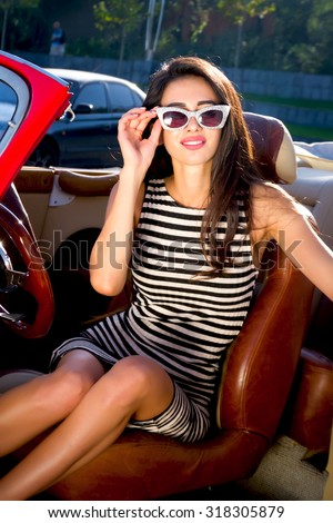 Summer Portrait of beautiful sexy stylish brunette girl model with bright makeup in retro style sitting in old car.Astonish young brunette woman sitting in retro car.Young woman driving on road trip  - stock photo