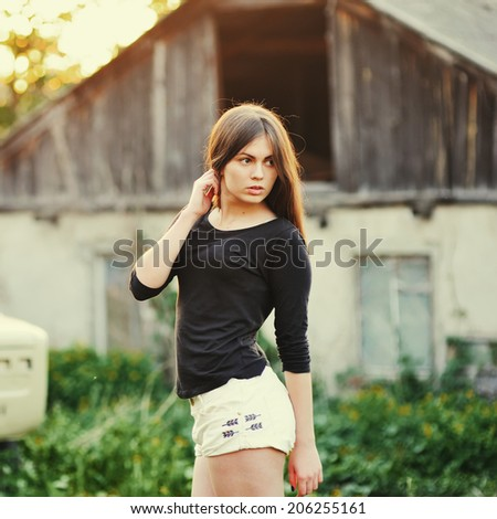 Summer portrait of brunette woman outdoor in backlit of sunset. - stock photo