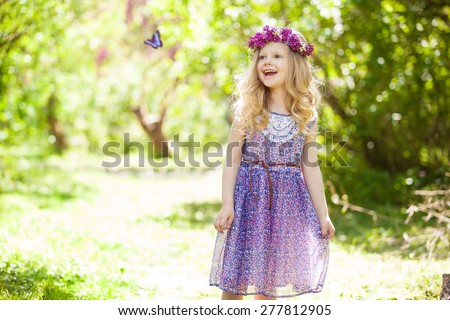 Summer portrait of cute blond girl dressed wreath of lilac on a head in green field with butterfly - stock photo