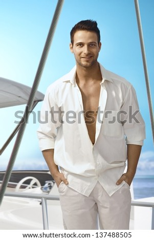 Summer portrait of handsome young man in white outfit standing on sailing boat, smiling happy. - stock photo