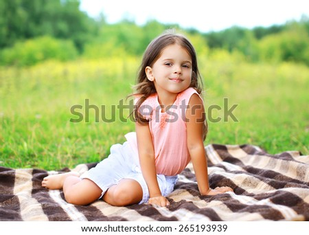 Summer portrait of happy little girl sitting on the plaid outdoors - stock photo