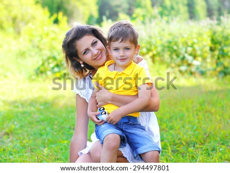 Summer portrait of happy mother and child son together on the grass
