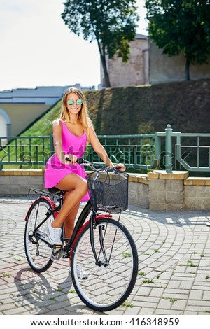 Summer portrait of pretty girl in pink dress on a bike  - stock photo