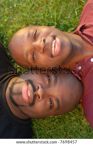 Summer portrait of two brothers lying side by side on the grass - stock photo